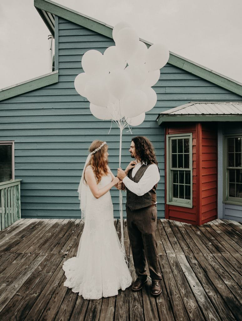 bride and groom facing each other while holding white balloons and bride's arm rest on groom's chest while they stand on a deck in front of a teal modern home in Dripping Springs, Texas