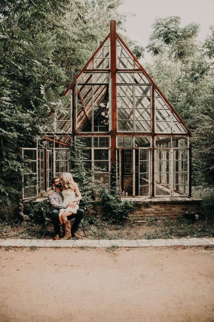bride to be sitting on groom to be's lap in front of glass house at Sekrit House in Austin, Texas