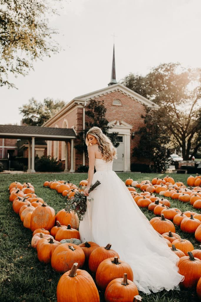 bride standing in a patch of pumpkins while holding her bouquet and looking over her shoulder in front of a church in West Austin, Texas