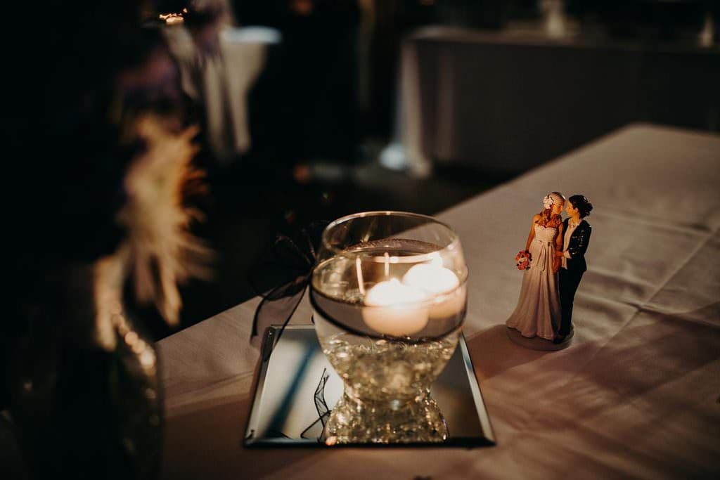Table with tea lights in a small glass of water and a cake topper of a bride with the groom at Chapel Dulcinea in Austin, Texas. Photograph by Austin, TX wedding photographer Nikk Nguyen.