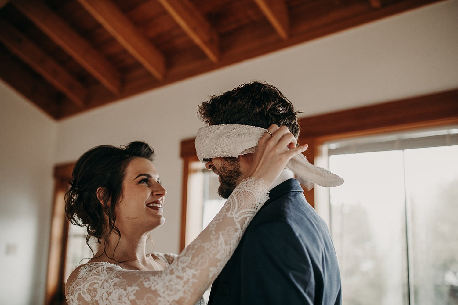 While smiling, the bride reaches to untie the towel from around the groom's eyes for surprise first look. Photograph by Austin, Texas wedding photographer Nikk Nguyen.