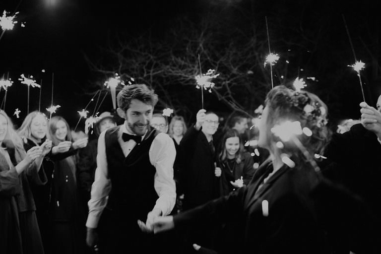 Black and white photo of bride and groom smiling at each other and holding hands while wedding guests hold lit sparklers around them. Photograph by Austin, TX wedding photographer Nikk Nguyen.