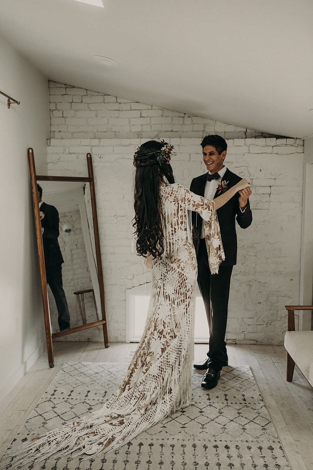 First look between bride and groom. Bride in a white bohemian dress and floral crown faces groom in a black tuxedo with a large smile on his face. Photograph by Austin, Texas wedding photographer Nikk Nguyen.