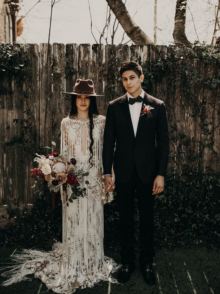 bohemian bride and groom holding hands and standing side by side while the bride holds her bouquet in front of a rustic wooden fence in Hutto, Texas