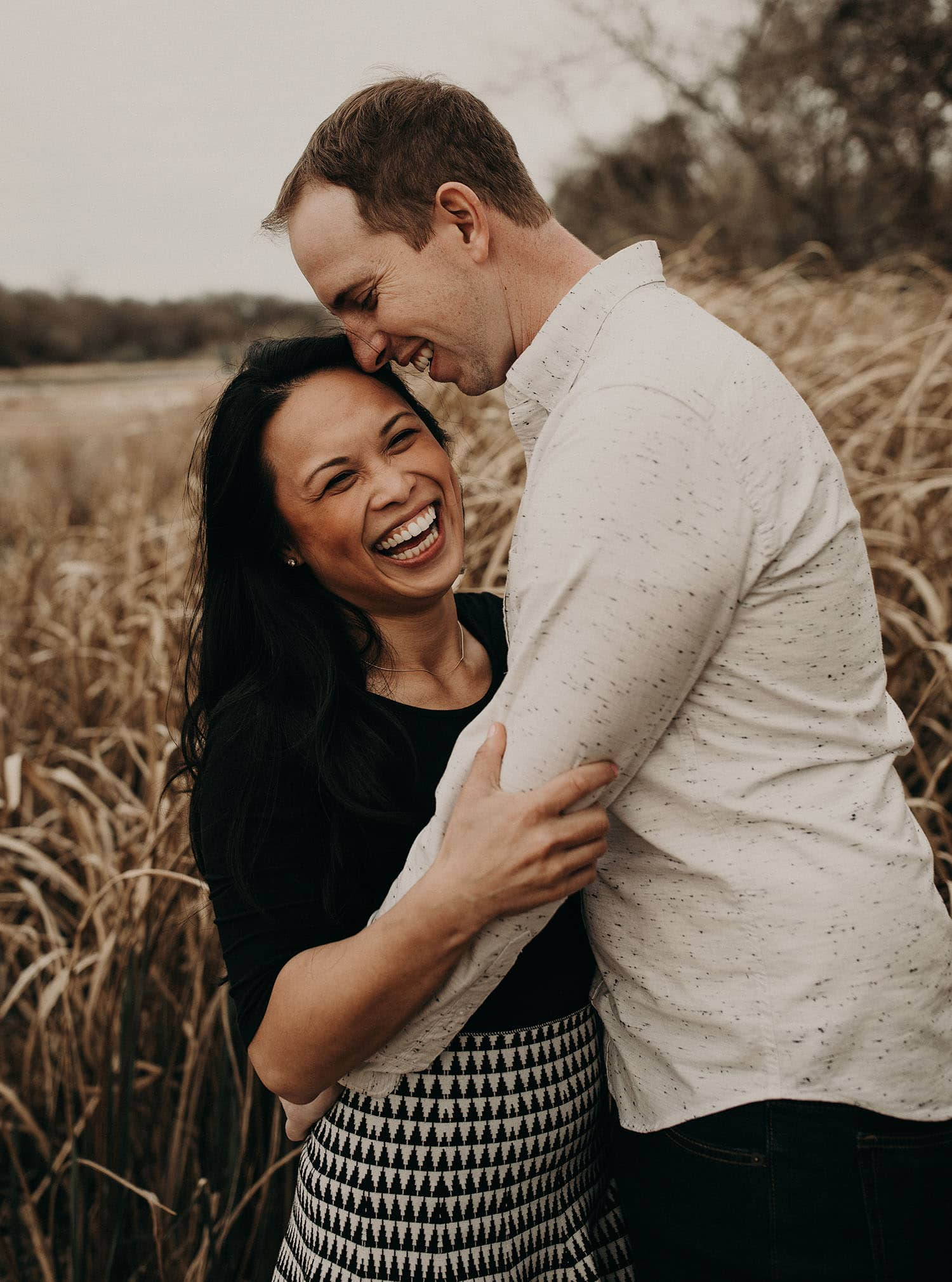 Engagement photo shoot with couple embracing each other as they smile and face each other while in a field of tall grass. Photograph by Austin, Texas wedding photographer Nikk Nguyen.