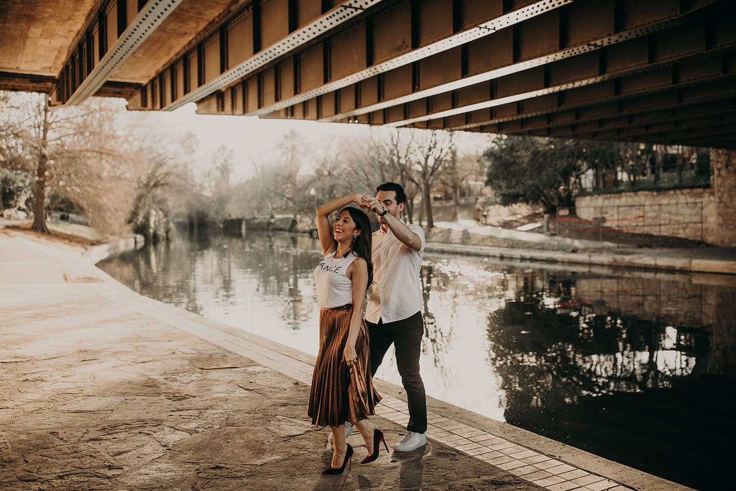 A male twirls female around as they dance under a bridge near a river in Austin, Texas. They are both smiling. Photograph by Austin, Texas wedding photographer Nikk Nguyen.