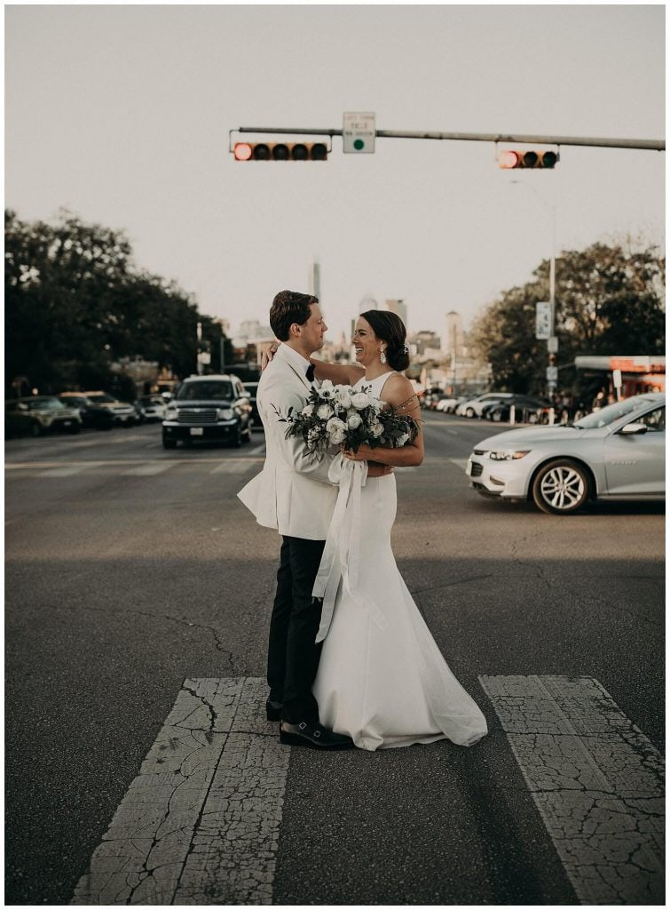 bride holds her bouquet while she embraces the groom in the middle of the crosswalk of a street in downtown Austin, Texas