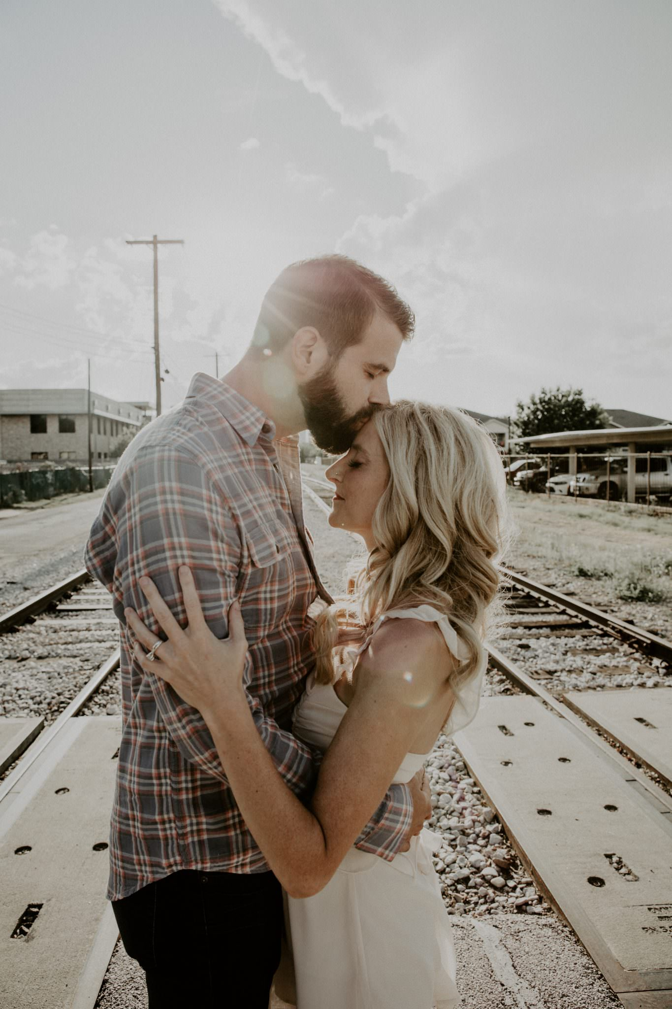 Engagement shoot with couple embracing with their eyes closed on railroad tracks with the sun shining behind them as the groom to be kisses the bride to be on the forehead. Photograph by Austin, Texas wedding photographer Nikk Nguyen.