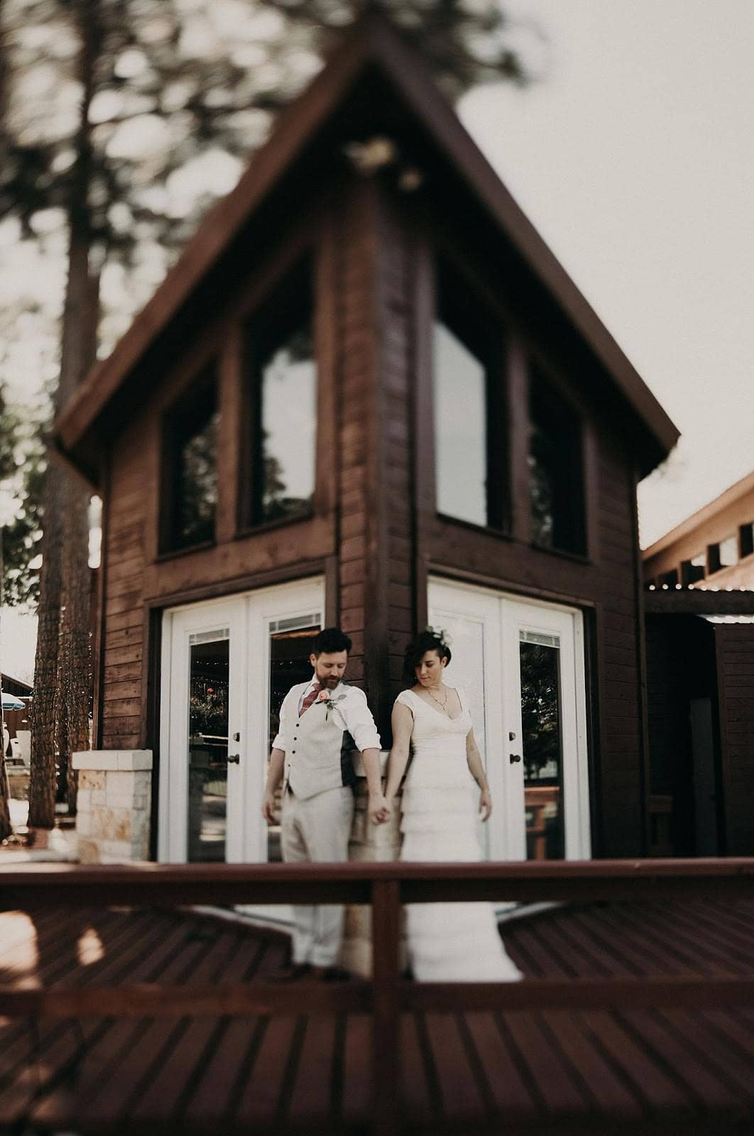 Bride and groom holding hands and looking at their intertwined hands while their backs are against adjacent walls of a dark brown lake house at Lake Buchanan outside of Austin, Texas. Photograph by Austin, Texas wedding photographer Nikk Nguyen.