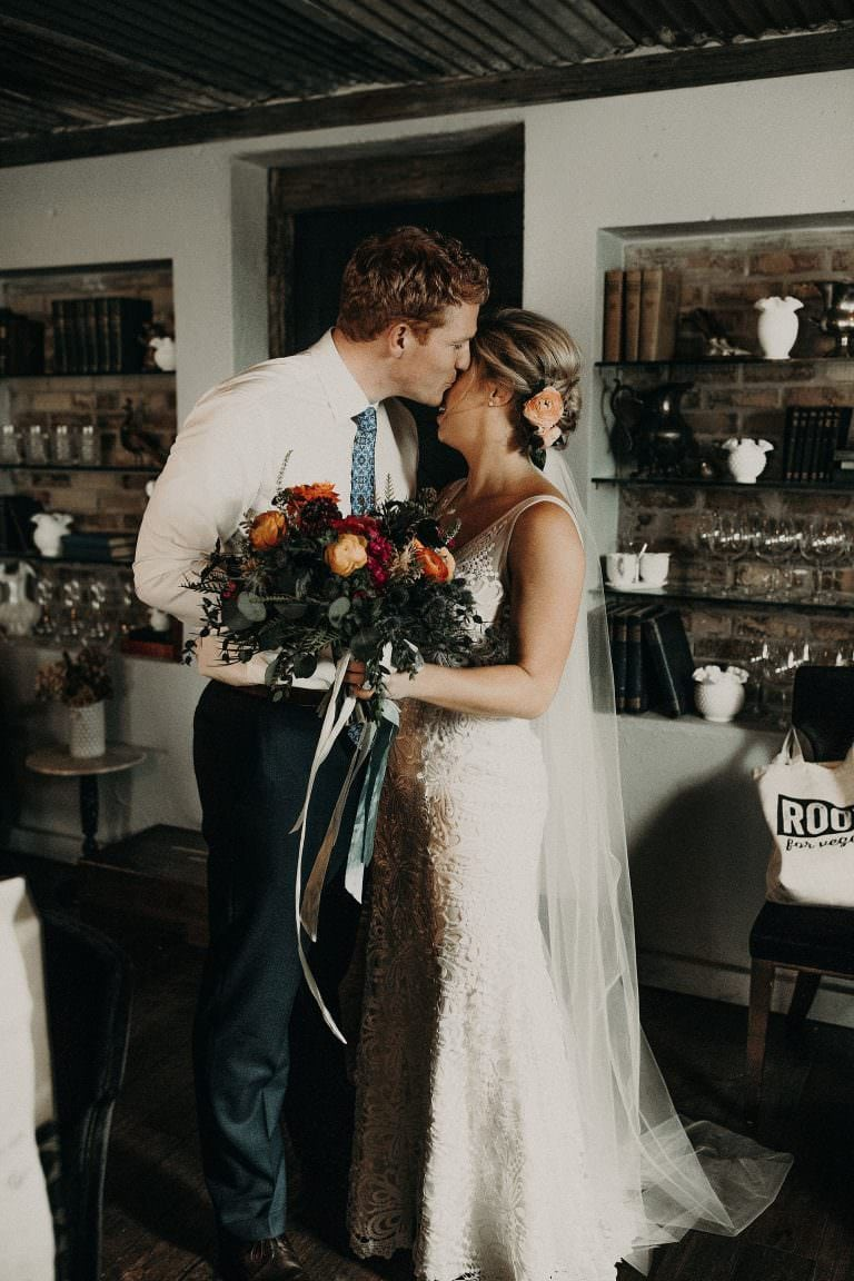 First look photo with bride holding her bouquet and groom kissing her on the cheek at Jacoby's Restaurant in Austin, Texas. Photograph by Austin, TX wedding photographer Nikk Nguyen.
