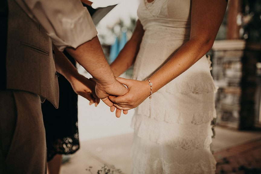 Close up of bride and groom holding hands while at the alter with their officiant during the ceremony. Photograph by Austin, Texas wedding photographer Nikk Nguyen.