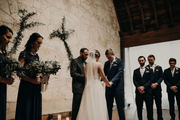 Bride and groom holding hands while praying at the altar with the officiant and surrounded by their bridal party at the Brodie Homestead in Sunset Valley, Texas. Photograph by Austin, TX wedding photographer Nikk Nguyen.