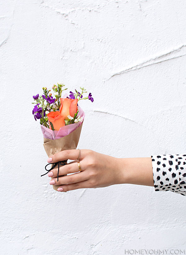 A female hand outstretched holding a mini bouquet of wildflowers and roses wrapped in tissue paper and a black ribbon against a white wall backdrop.