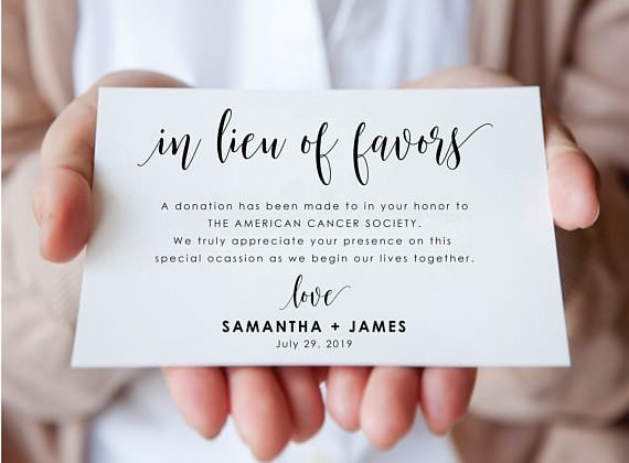 "Two hands holding card stock of a favor donation that says ""in lieu of favors a donation has been made to in your honor to THE AMERICAN CANCER SOCIETY. We truly appreciate your presence on this special ocassion as we begin our lives together. Love Samantha + James July 29, 2019""."