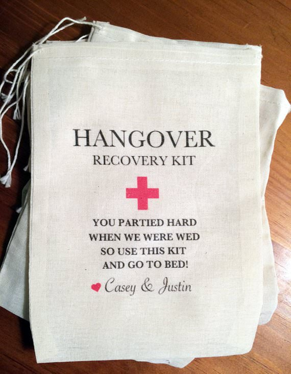 "A pile of small ""hangover recovery kit"" drawstring bags that say ""you partied hard when we were wed so use this kit and go to bed, Casey & Justin""."