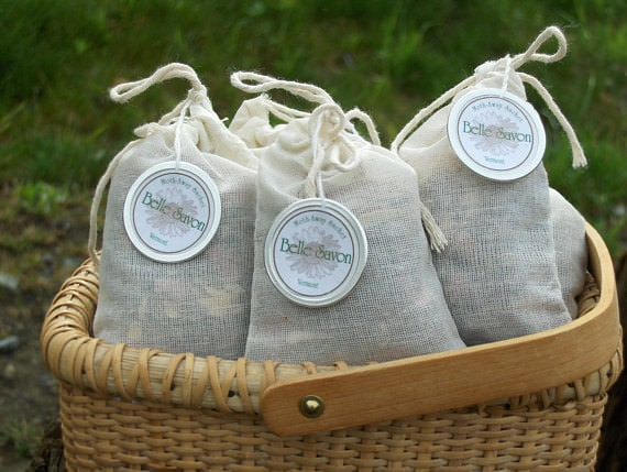 Three small burlap sachets containing herbs and spices placed in a small basket on the grass.