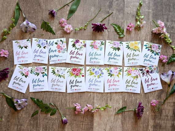 """Various flower seed packets that say """"let love grow"""" spread in two rows on a hard wood floor surrounded by various wildflowers."""