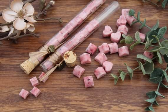 Pink hibiscus vanilla sugar heart shaped cubes displayed on a wooden floor scattered and in tubes surrounded by hibiscus flowers and some leafy branches.