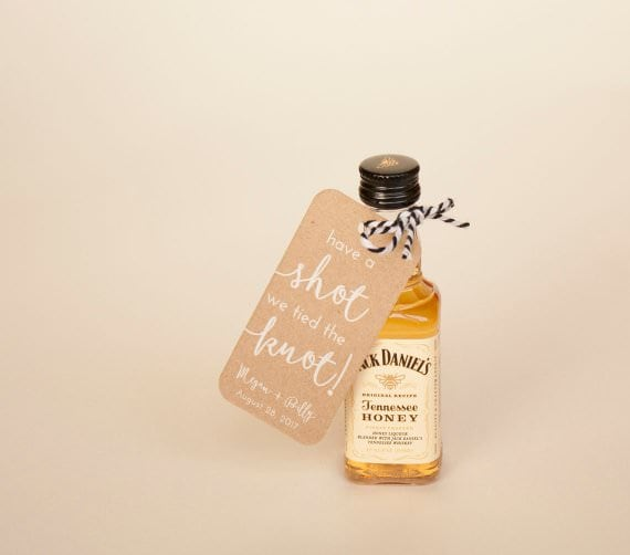 """A favor sized bottle of Jack Daniel's Tennessee honey whiskey with a note tied around it's neck that says """"Have a shot we tied the knot!"""" against a cream backdrop."""