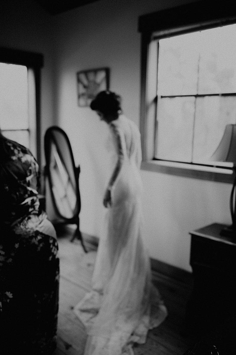 Black and white off-focus photo of a bride standing in front of a small stand up mirror at House on the Hill in Austin, Texas. Photograph by Austin, Texas wedding photographer Nikk Nguyen.