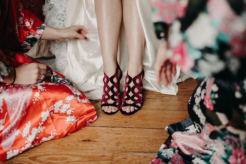 bride's feet in velvet dark red heels as two bridesmaids kneel in silk kimonos to arrange the bottom of her dress for the shot