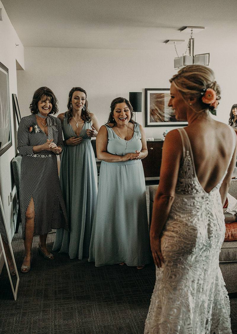 A bride smiling as two of her bridesmaids and her mother admire her in her wedding dress in Austin, Texas. Photograph by Austin, Texas wedding photographer Nikk Nguyen.