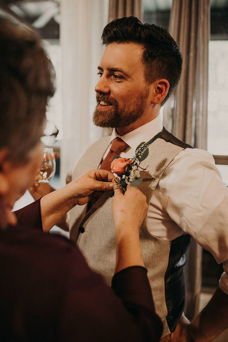 a smiling groom smiles and holds his drink as an older woman attaches his boutonniere