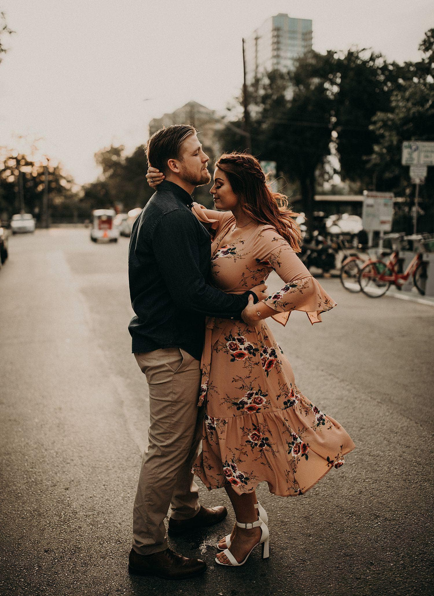 Bride to be and groom to be embrace with their eyes closed in the middle of the street during the golden hour in downtown Austin, Texas. Photograph by Austin, Texas wedding photographer Nikk Nguyen.