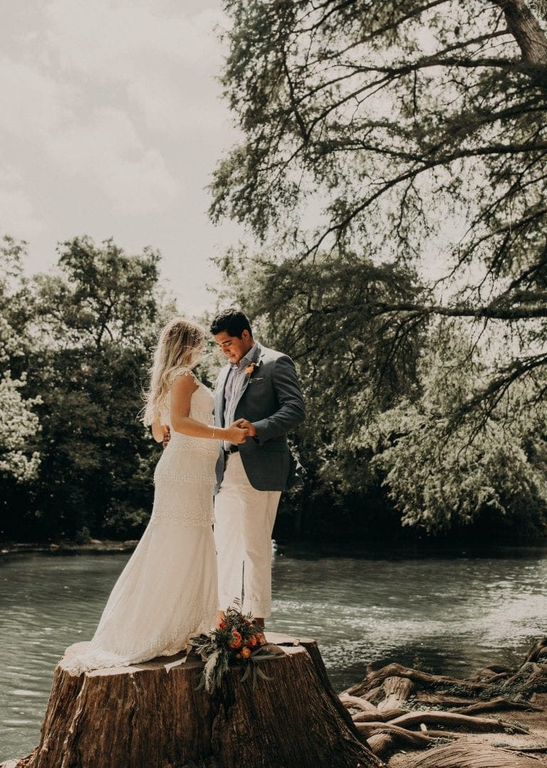 Bride and groom holding hands and facing each other while standing on a tree trunk in front of the San Marcos River in Texas. Photograph by Austin, TX wedding photographer Nikk Nguyen.