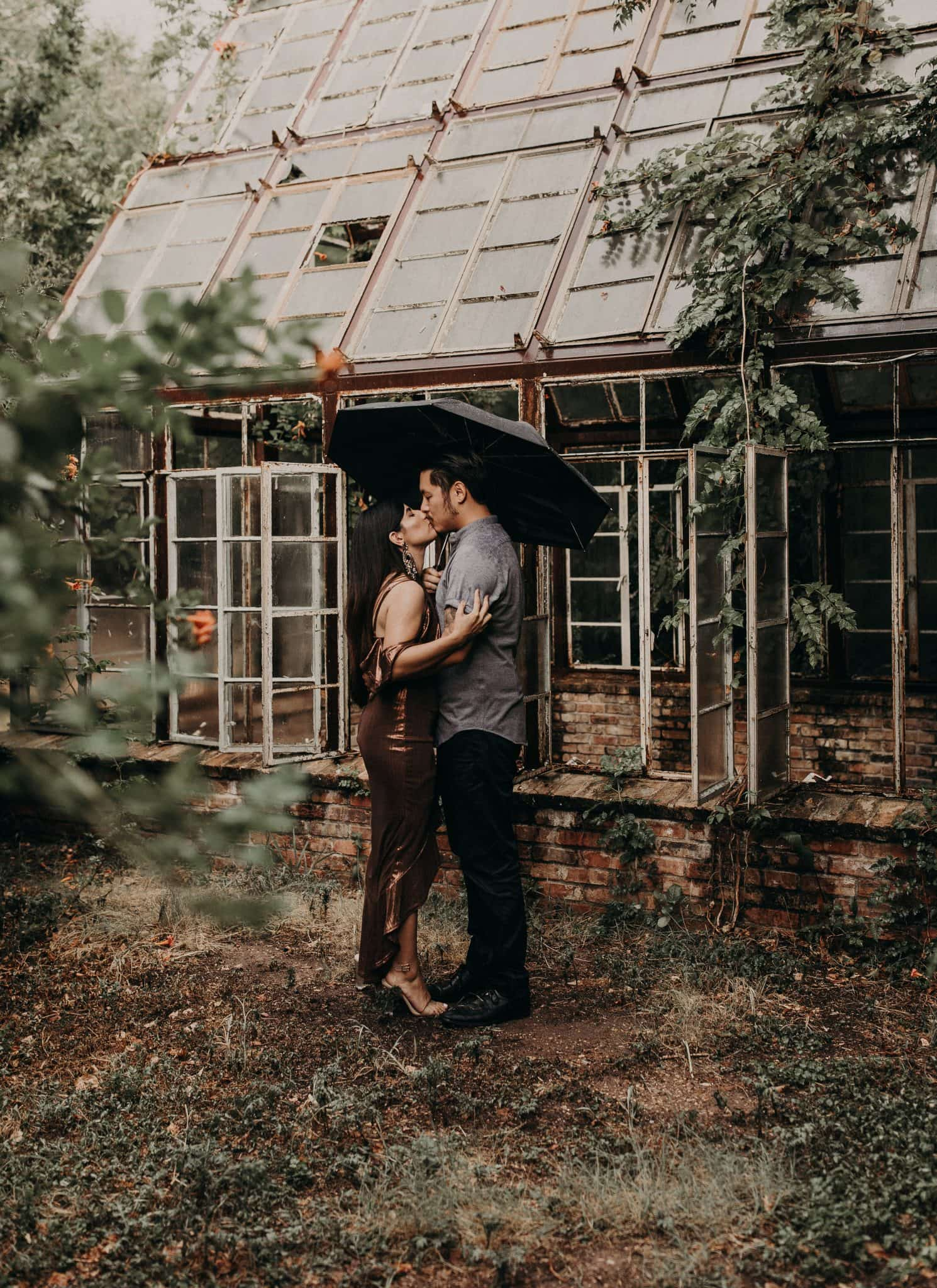 Bride to be and groom to be standing in front of an old brick and rustic greenhouse with it's windows open while holding an umbrella and kissing at Sekrit Theater in Austin, Texas. Photograph by Austin, Texas wedding photographer Nikk Nguyen.