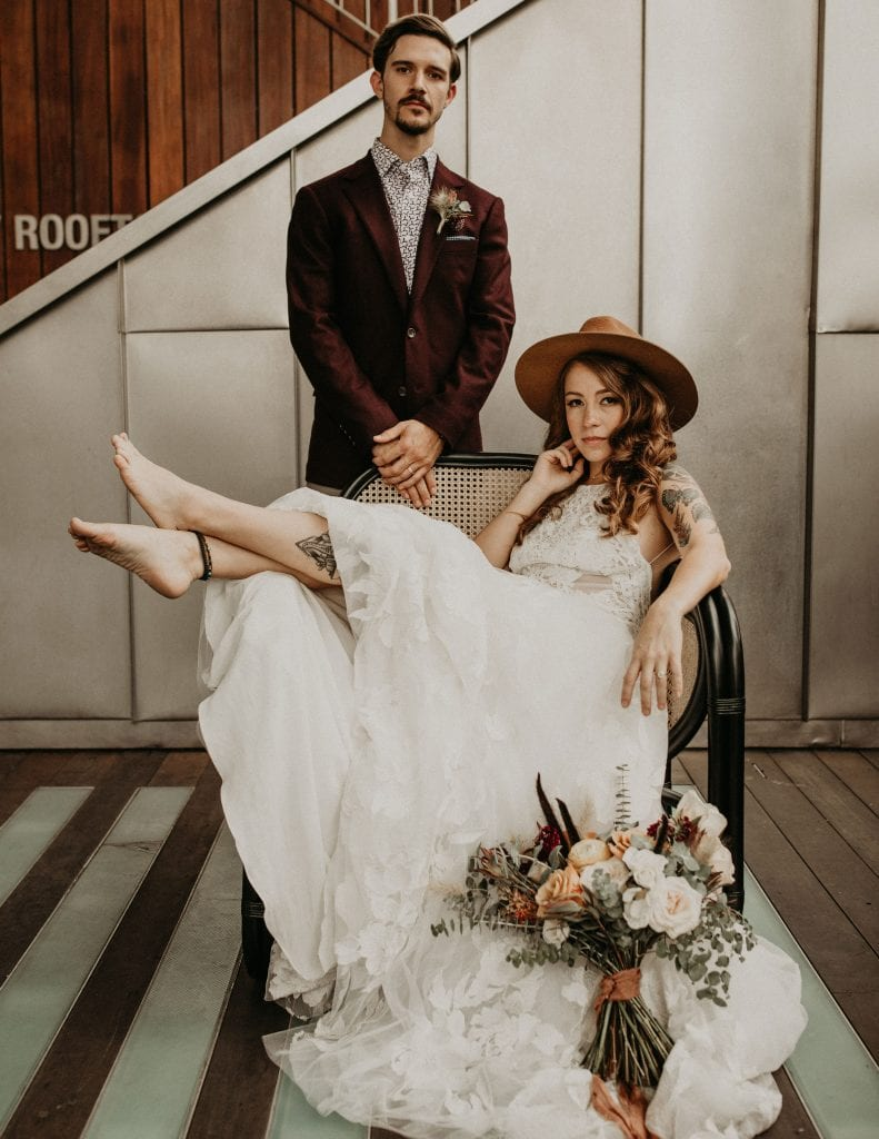 bohemian bride lounges in a vintage chair with her bouquet on the floor in front of her while groom stands behind her at The Contemporary Austin - Jones Center in Austin, Texas