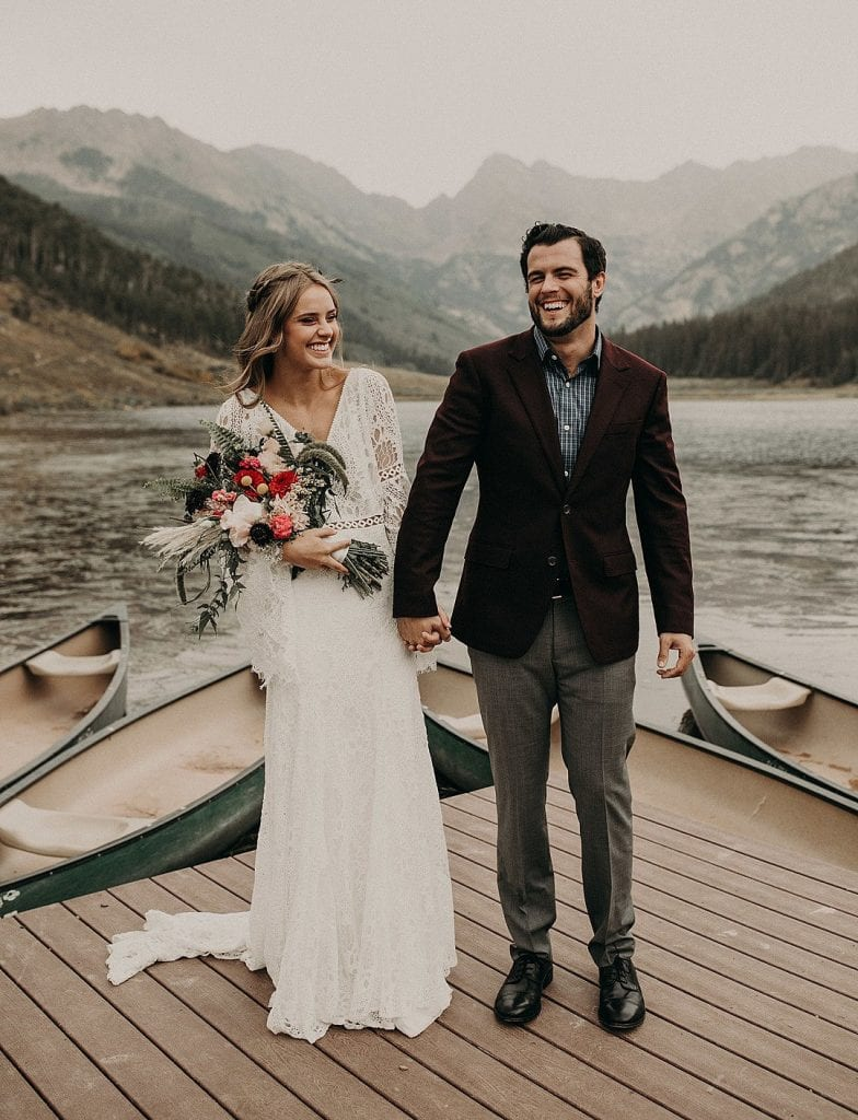 Bride and groom smiling and holding hands while standing on a dock in front of 4 canoes as the bride holds her bouquet with a Piney lake and mountain backdrop at Piney River Ranch in Vail Colorado. Photograph by Austin, Texas wedding photographer Nikk Nguyen.