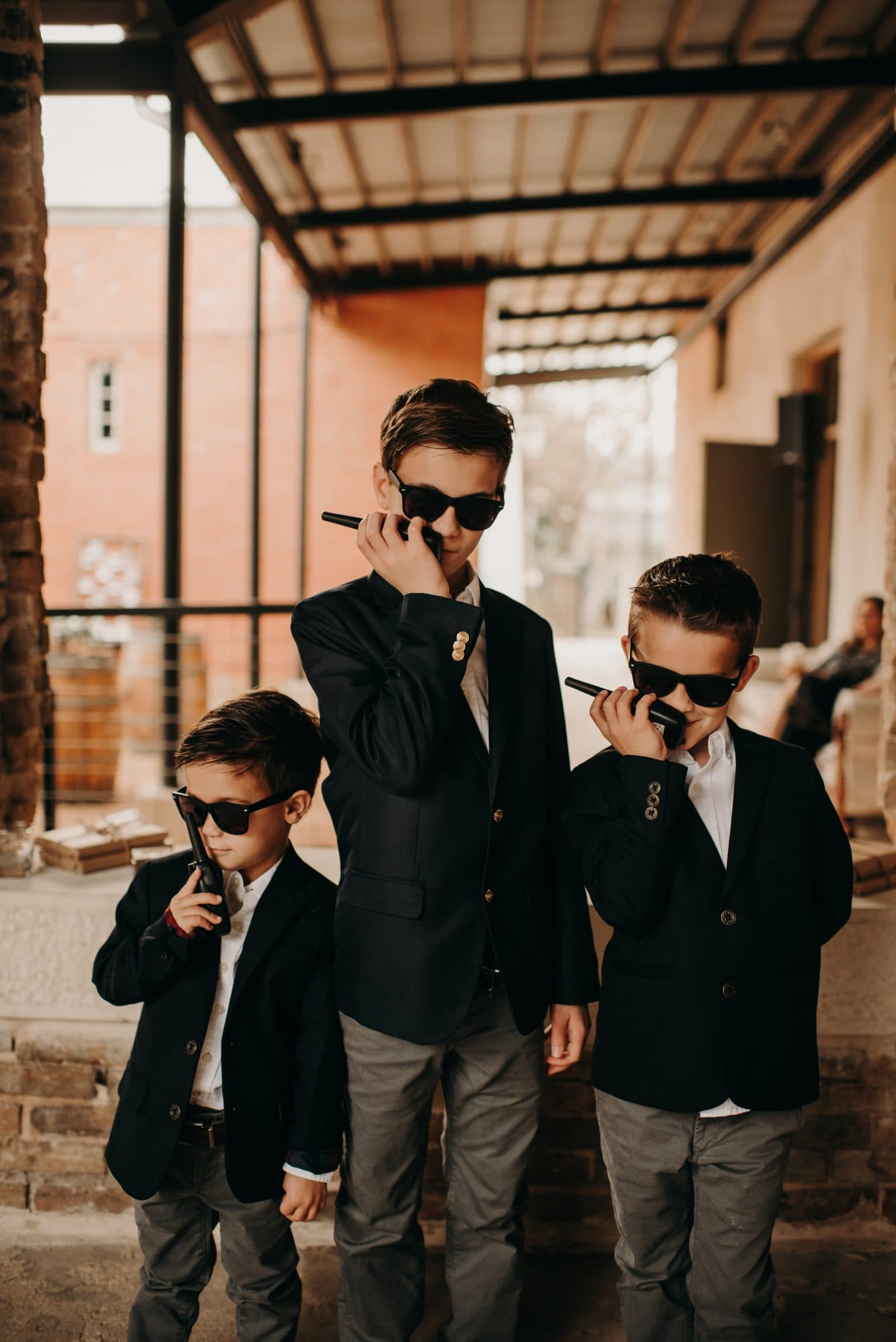 Portrait of 3 boys in matching suits and sunglasses pretending to talk on two way radios at the Ingenhuett on High in Comfort, Texas. Photograph by Austin, Texas wedding photographer Nikk Nguyen.