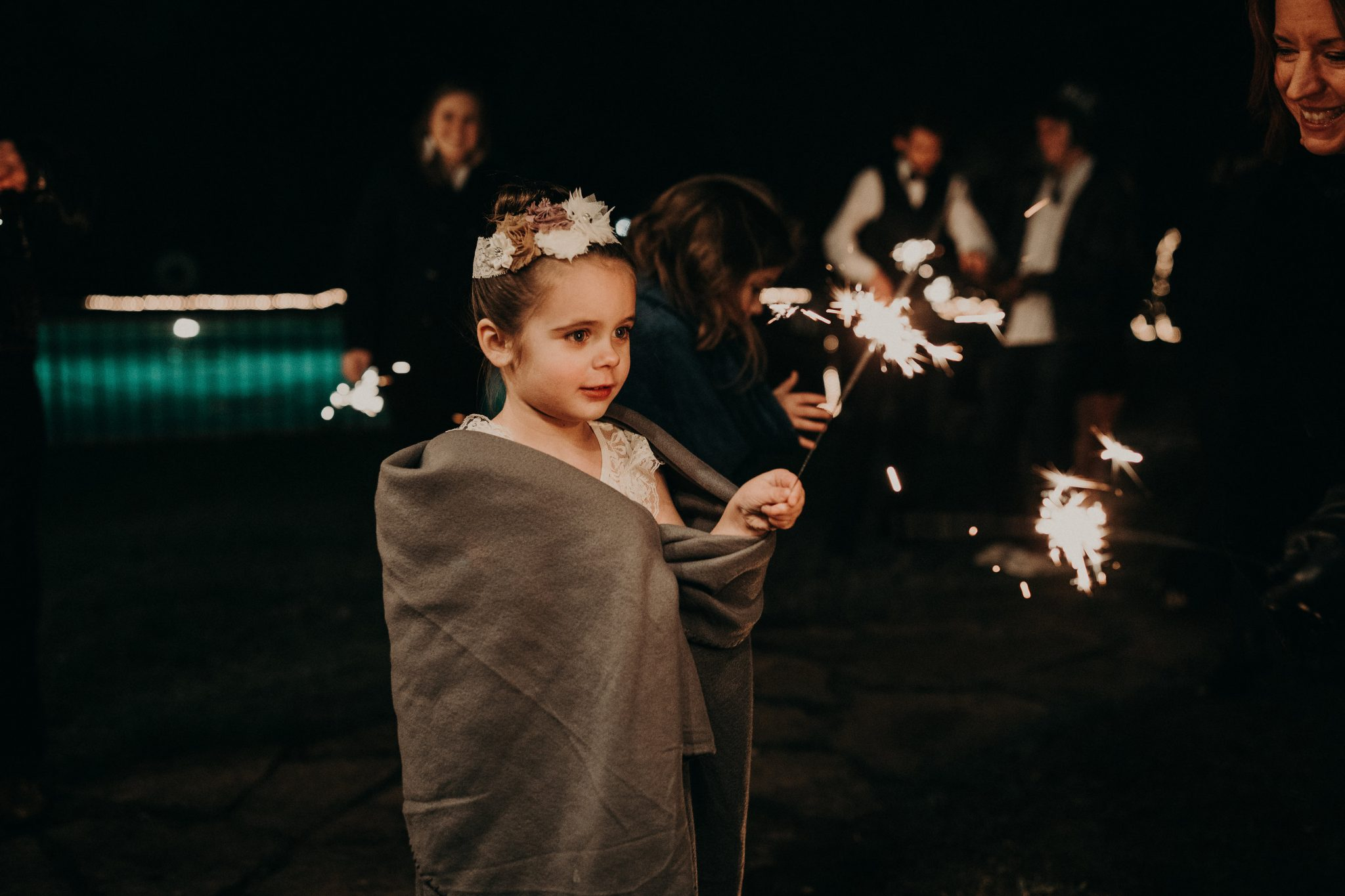 A little girl with a flower headband and wrapped in a blanket staring at the lit sparkler she is holding with people in the background and a women off to the side smiling at her at House on The Hill in Austin, Texas. Photograph by Austin, Texas wedding photographer Nikk Nguyen.