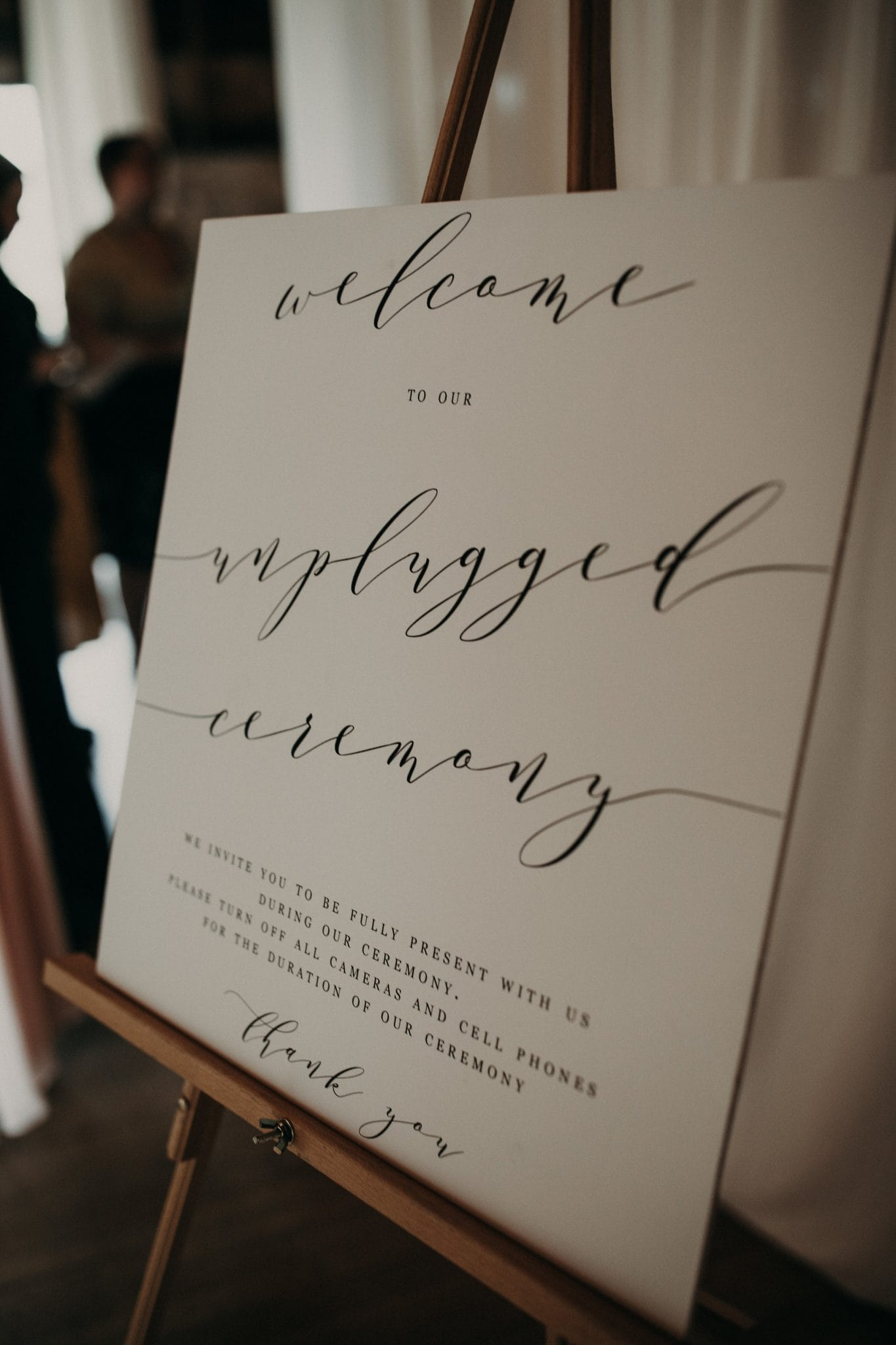 """Easel holding a poster that says """"welcome to our unplugged ceremony we invite you to be fully present with us during our ceremony. please turn off all cameras and cell phones for the duration of our ceremony thank you"""". Photograph by Austin, Texas wedding photographer Nikk Nguyen."""