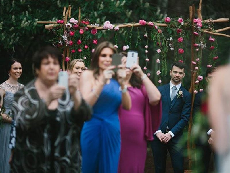 Off focus shot of 3 women taking photos with their iPhones of the bride as she walks down the isle while blocking the bridal party from seeing the bride and the groom leaning out from behind them to see the bride walk down the aisle.