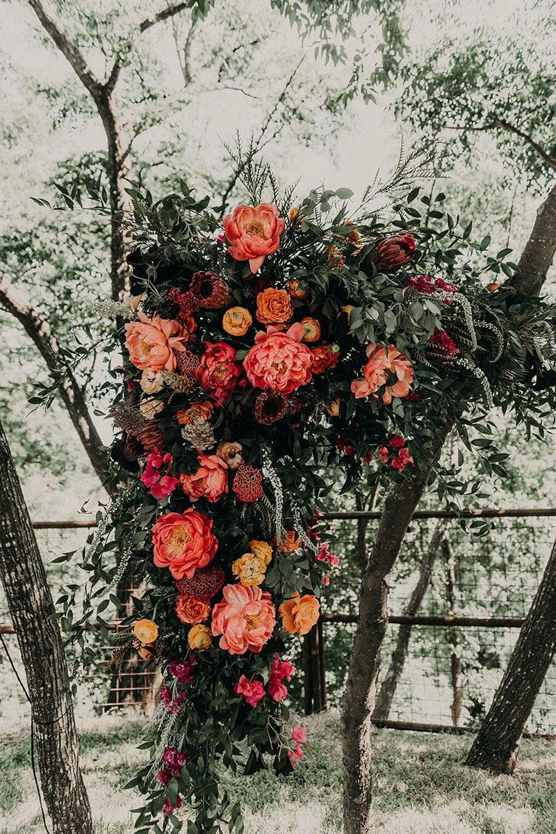 A large bouquet of red, orange, and pink flowers hanging from a tree in Austin, Texas. Photograph by Austin, Texas wedding photographer Nikk Nguyen.