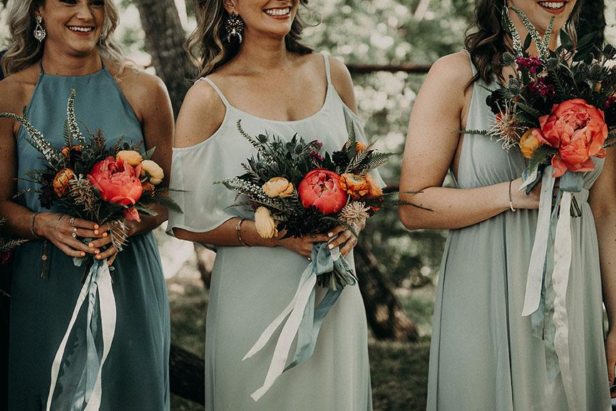 Three bridesmaids in teal and mint colored bridesmaid dresses holding small bouquets of orange, red, and pink flowers tied with a mint bow while smiling in Austin, Texas. Photograph by Austin, Texas wedding photographer Nikk Nguyen.