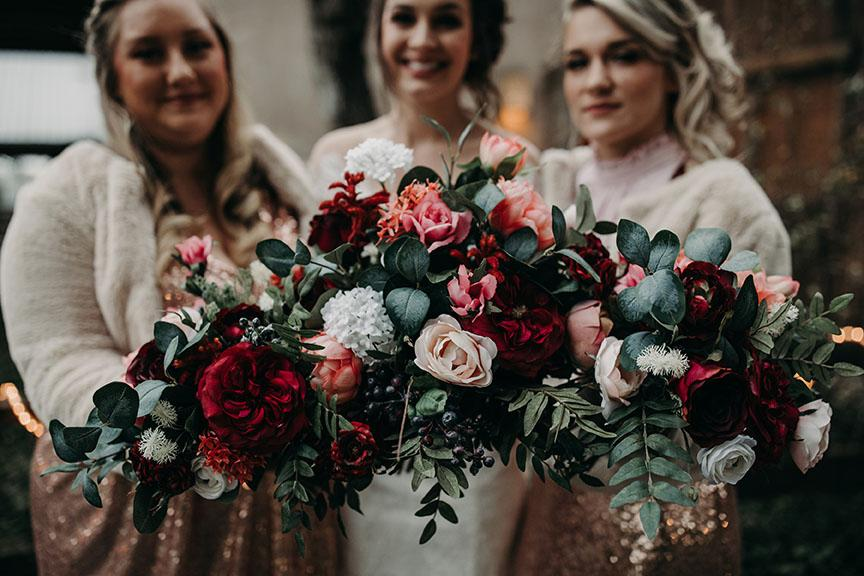 Two bridesmaids standing on either side of the bride while they smile and extend their bouquet's for a close up shot at House on The Hill in Austin, Texas. Photograph by Austin, Texas wedding photographer Nikk Nguyen.