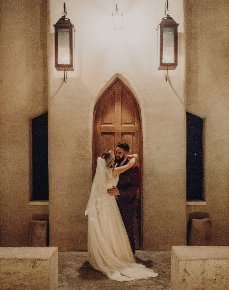 Bride and groom embracing at the altar of Chapel Dulcinea in Austin, Texas at night. Photograph captured by Austin, Texas wedding photographer Nikk Nguyen.