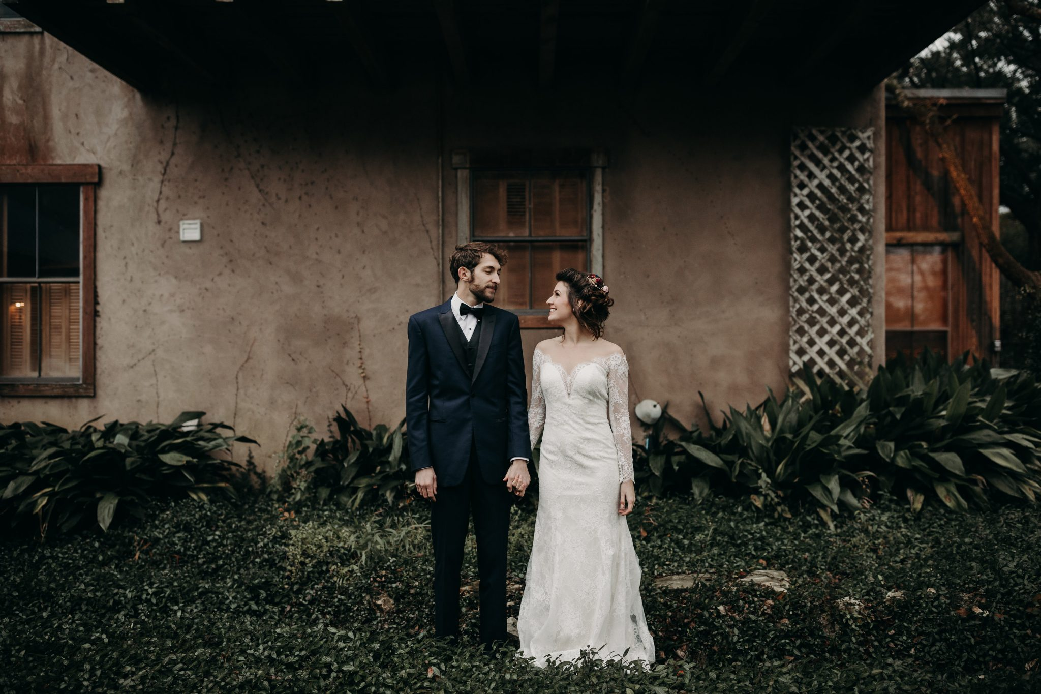 Bride and groom holding hands side-by-side and smiling at each other while standing in the grass in front of the side of a rustic house at House on the Hill in Austin, Texas. Photograph by Austin, Texas wedding photographer Nikk Nguyen.