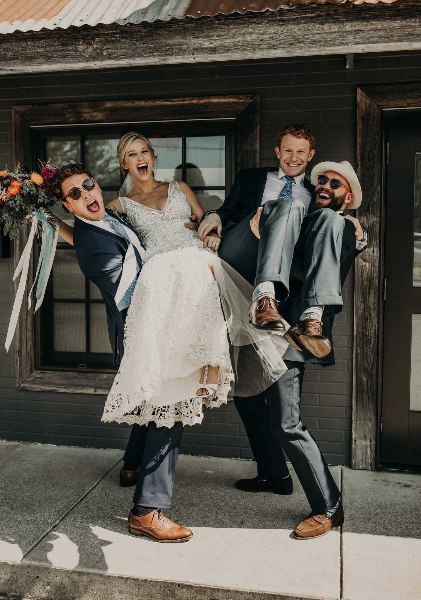 Two smiling groomsmen carrying a smiling and laughing bride with her bouquet and groom on the patio of a rustic home at Jacoby's restaurant in Austin, Texas. Photograph by Austin, Texas wedding photographer Nikk Nguyen.