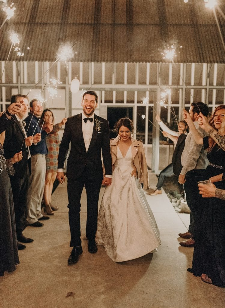 bride and groom exiting Prospect House in Dripping Springs, Texas while wedding guests hold sparklers around them