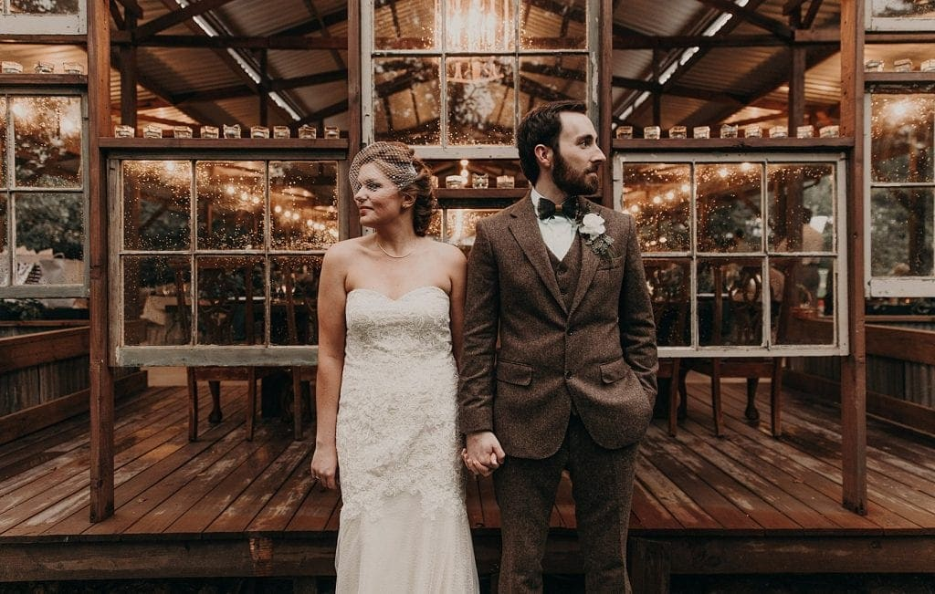 Bride and groom holding hands and standing side by side with their heads turned away from each other in front of windows on the side of a rustic barn at the Homestead at Old Potato Road in Paige, Texas. Photograph by Austin, Texas wedding photographer Nikk Nguyen.