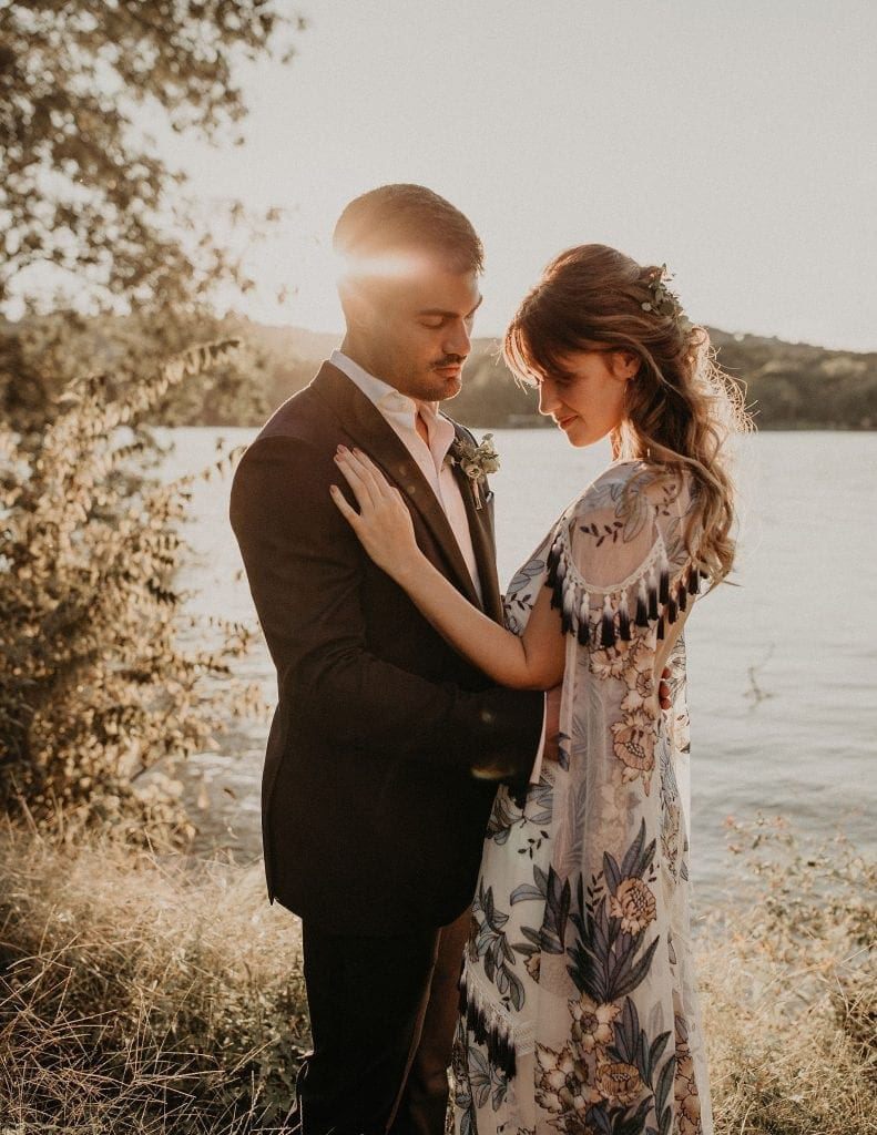 bohemian bride and groom embracing at the golden hour on the shore of the lake at The Contemporary Austin - Laguna Gloria in Austin, Texas