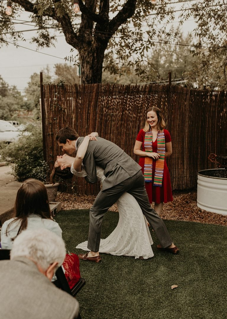 Groom embraces the bride as he bends her over to go in for a kiss at the altar with officiant behind them outside at Lenoir Restaurant in Austin, Texas. Photograph by Austin, Texas wedding photographer Nikk Nguyen.
