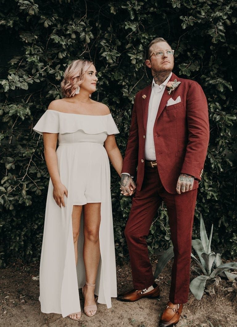 Bride and groom standing side-by-side while holding hands as the bride looks at the groom who is looking toward the right and they are standing in front of tall green bushes at Justine's Secret House in Austin, Texas. Photograph by Austin, TX wedding photographer Nikk Nguyen.