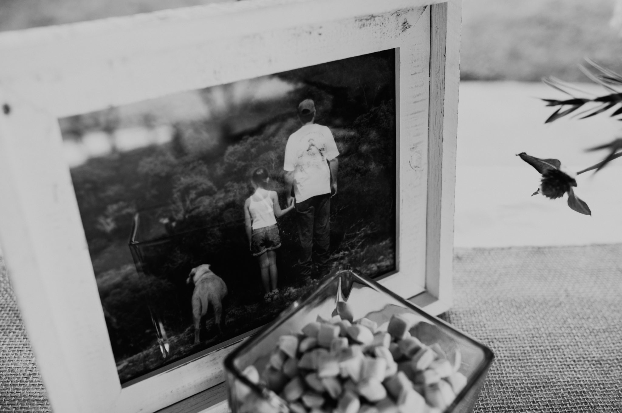 Black and white photo of a table with a glass bowl of favors and a white framed photo of a dog, small girl, and father standing together. Photograph by Austin, Texas wedding photographer Nikk Nguyen.