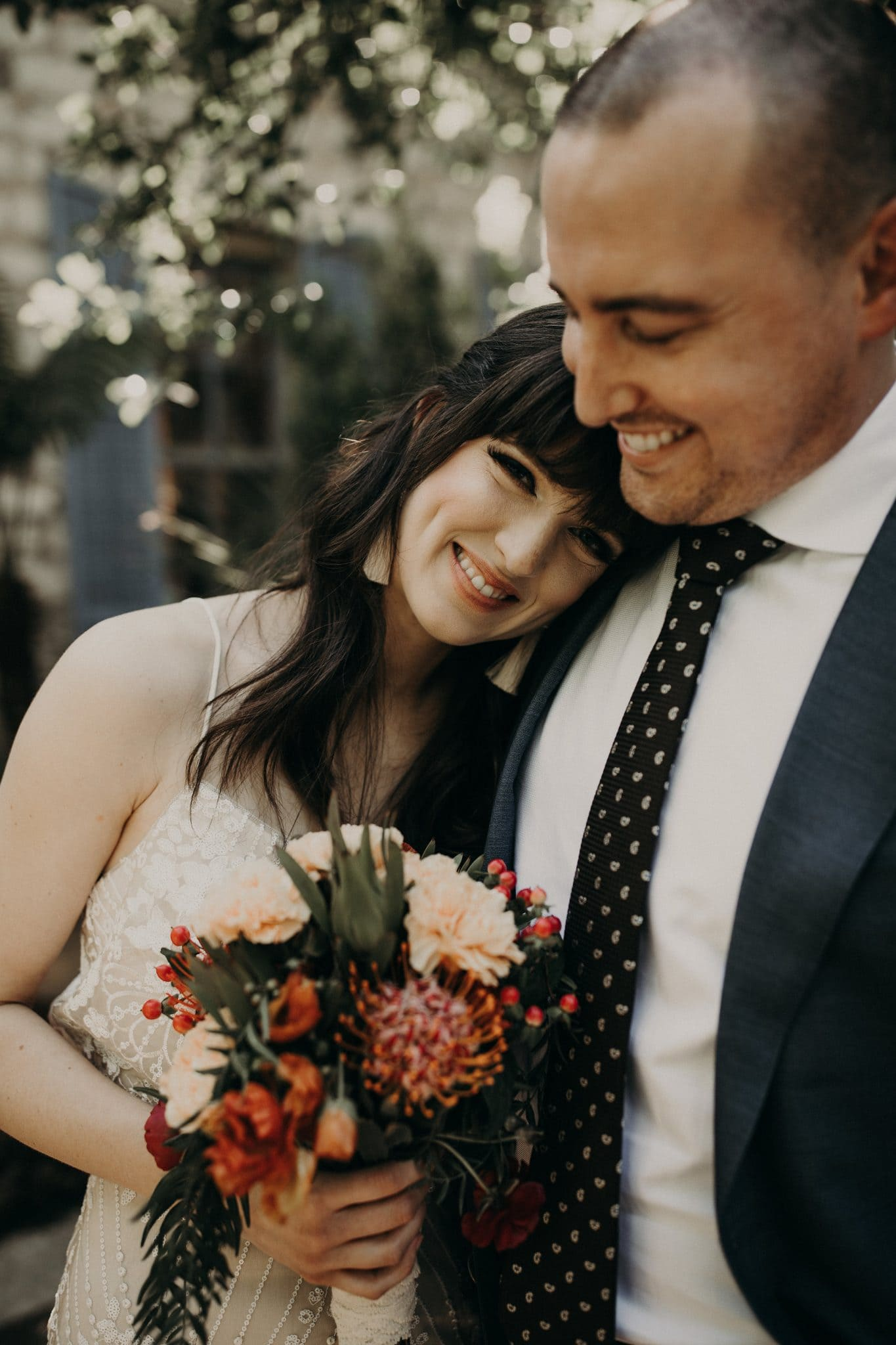 Bride smiling and holding her bouquet as she leans against the right side of the grooms chest and he smiles down at her in Austin, Texas. Photograph by Austin, Texas wedding photographer Nikk Nguyen.