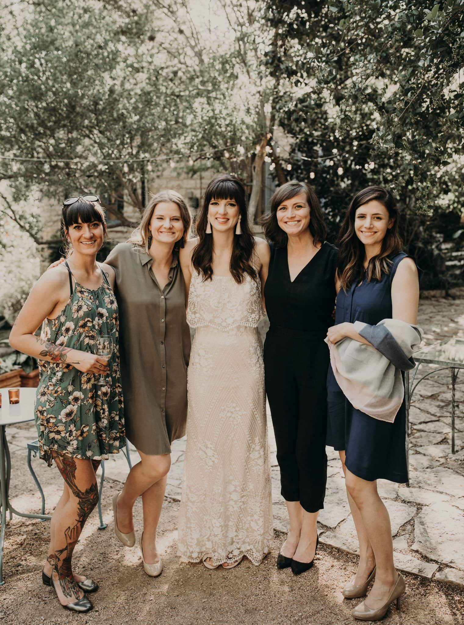 Bride and her female friends standing side-by-side and smiling at the camera while in a patio with cobblestone flooring and trees in the background. Photograph by Austin, Texas wedding photographer Nikk Nguyen.
